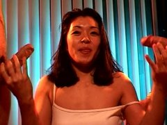 Asian hottie giving double handjob