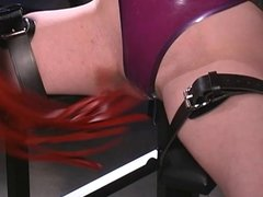 Latex mistress punishes captured brunette