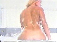Pretty blonde masturbates while having a bubble bath