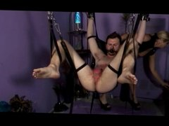 Dominatrix pours hot wax on bondaged guy's cock