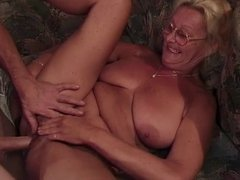 Mature blonde with glasses sucks a cock