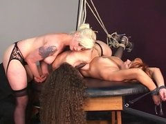 Blonde redhead and brunette BDSM slaves bound to and hung over table by old man