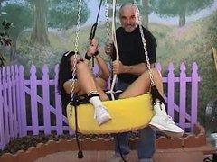 Sexy slut on a bondage swing by fence