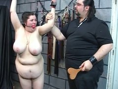 Guy in clothes punishes naked girl in dungeon