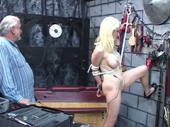 BDSM pale blonde with clamp on her clit stands so dude can clamp her nipples