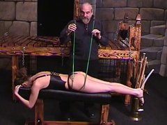 Corseted brunette lies down on bench so dude can cane her ass