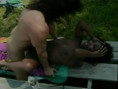Black girl sucks cock and gets cunt fucked and licked on the lawn bench