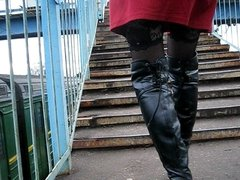 Girl in stockings and black leather boots going upstairs