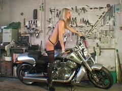 Blonde girl strips and poses on a motorbike
