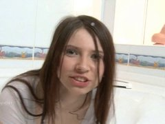 Young natural brunette strips in the bathtub and dildoing
