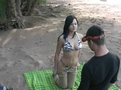 Titted brunette sucks on the beach