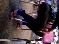 Ebony lady with long toenails on sandals.