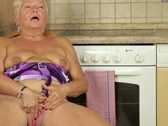 Blonde granny doing herself in the kitchen