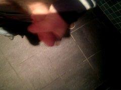 Wanking in a public toilet.