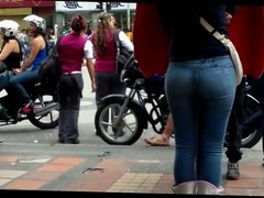 a beautiful round ass in jeans talking at a public phone