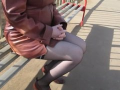 Girl in seamed stockings going upstairs on a train station