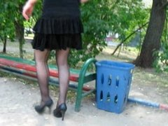 Girl in seamed stockings walking and seating on the bench