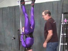 suspended in purple catsuit