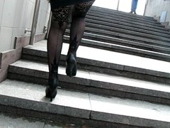 Girl in fashion fishnet stockings going upstair