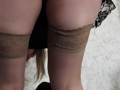 Girl in stockings puts on a skirt
