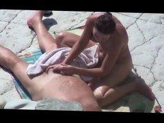 Girl does a guy Jerks Off dick on a public beach