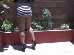 A lady in a shiny day with 5 inch heels in pantyhose