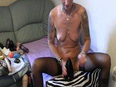 Tattooed woman riding a huge butt plug.