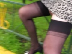 Girl in leopard skirt and stockings sitting on a fence