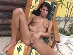 Skinny babe fingers her pussy outdoors