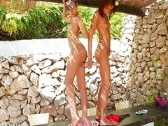 Lesbo couple sharing double dildo outdoor