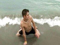 Handsome boy JJ lies on an ocean coast