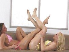 Two sensual oiled up babes in bikini