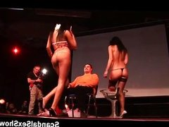 Two brunette strippers give a lap dance