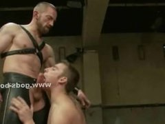 Gay man with hands fixed with ropes on a planket gets abused and