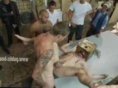 Gay hunk bound on a table with head locked in wooden cage is ramm