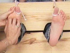 Cute girl gets her feet tickled in stocks