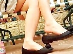 Sexy legs her feet dangling with her black flat shoes
