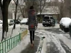 Sexy girl in black leggings walking barefoot on the snow