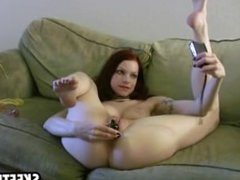 A sexy redhead fingersherself on the couch