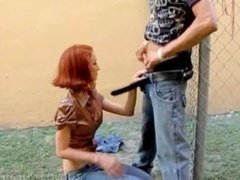 Topless redhead tugging hard cock thru a fence
