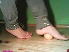 Girl crushing a mandarin orange with her feet