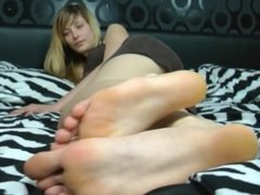 Girl teases you with her soles on a bed