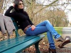 une bombe en jean et talon qui marche dans un park