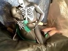 fantasy scene where spandex skeleton wrestles and humps frogman