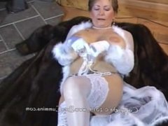 Mature lady satisfies herself on a fur coat.