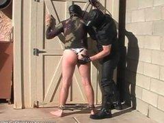 Spanking guy on leash outdoors