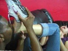 Sweaty bare feet in sneakers get licked