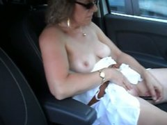 nue en voiture sur un parking public