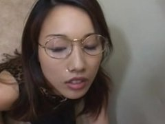 Desirous Japanese cowgirl in glasses has her face covered in cum after delivering a spicy handjob