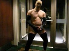 stocking masked biker jerks off in hotel hall